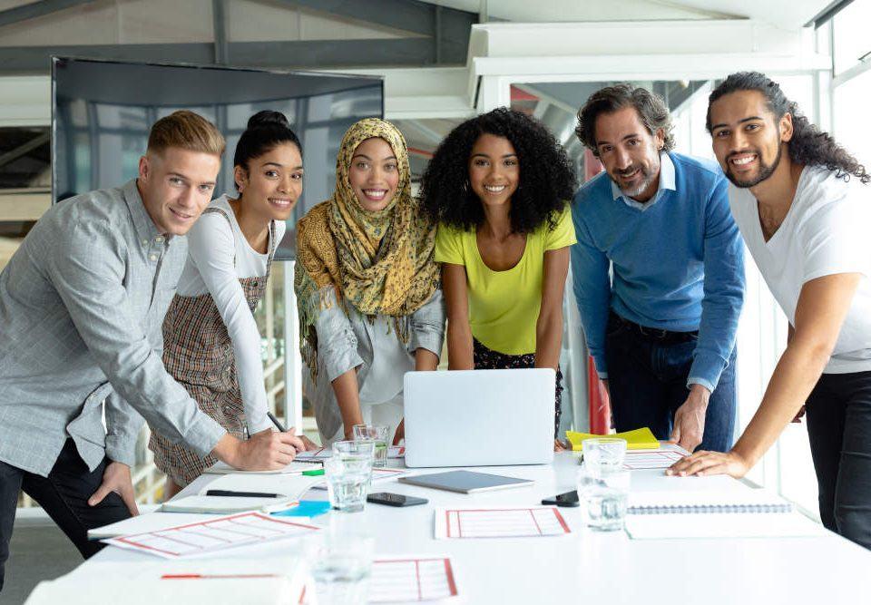 Diversity am Arbeitsplatz: Ein sechsköpfiges Team, drei Frauen und drei Männer unterschiedlichen Alters und Herkunft stehen vor einem Schreibtisch in einem Büro und lächeln in die Kamera