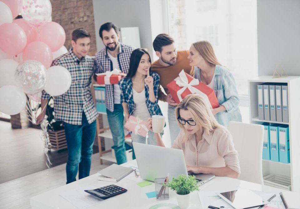 Geschenke fürs Büro: Fünf Kollegen schleichen sich mit Luftballons und verpackten Geschenken an den Schreibtisch einer Kollegin heran, um sie zu überraschen