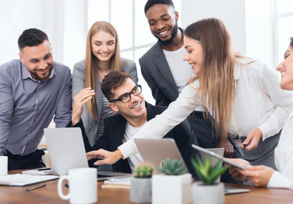 Erfolgreich sein in der VUCA Welt: Ein Team aus drei Männern und drei Frauen sitzt um einen Laptop herum und diskutiert angeregt