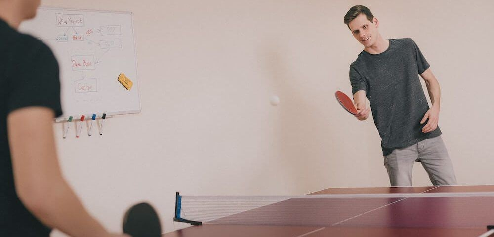 Zwei Angestellte spielen Tischtennis im Büro