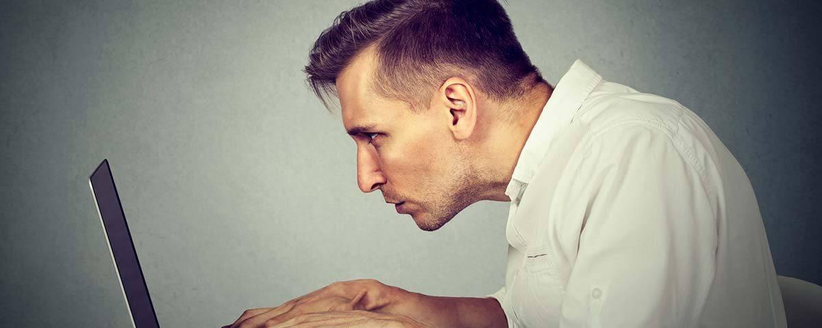 Mann sitzt in gebeugter Haltung vor dem Laptop