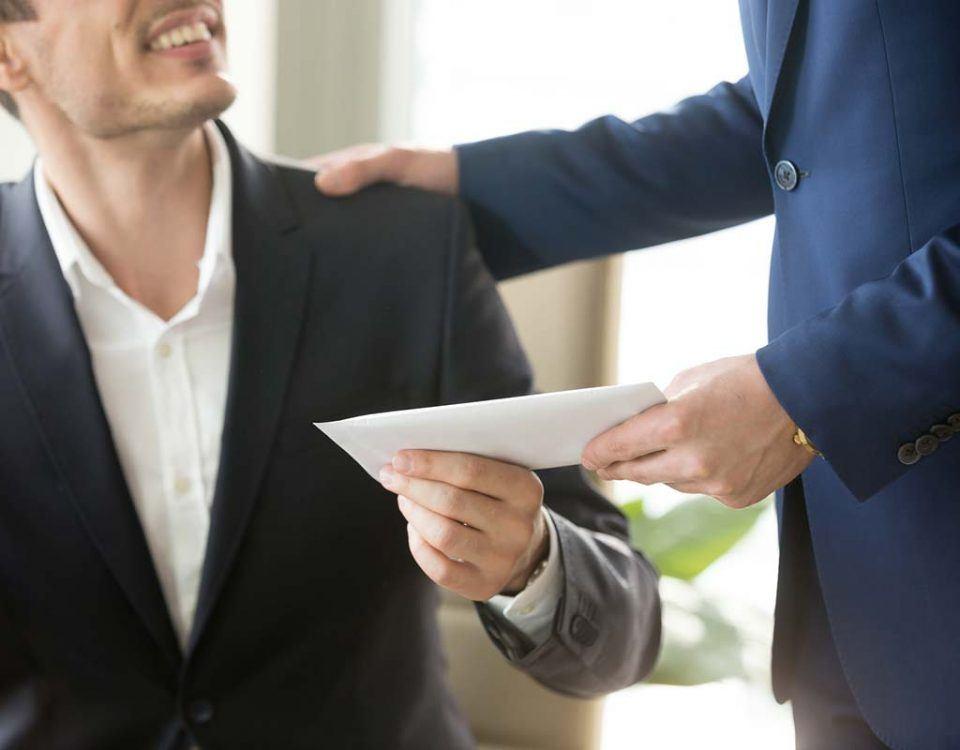 Mann überreicht einen Umschlag an einen anderen Mann