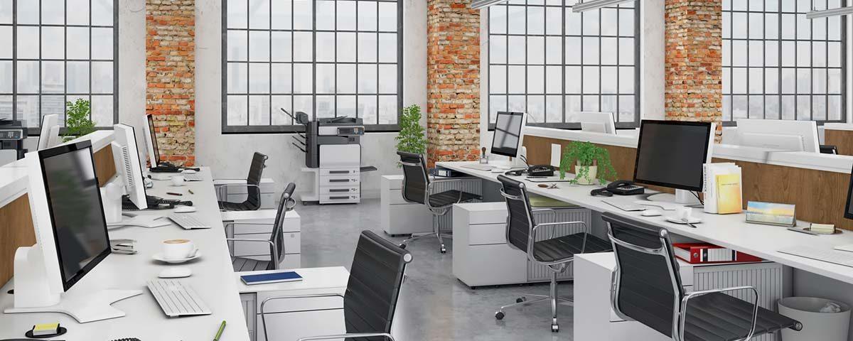 Großraumbüro mit Tischen, Stühlen und PC-Monitoren
